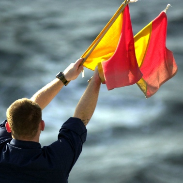 Man signalling with two red and yellow semaphore flags