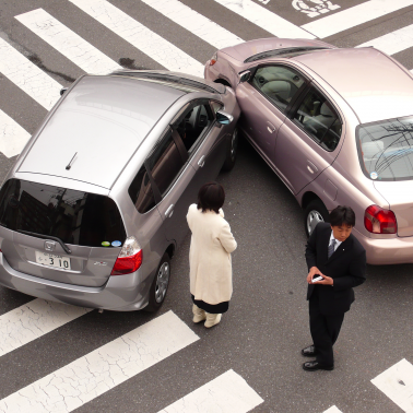 Aftermath of a fender bender in an intersection with drivers and their cell phones