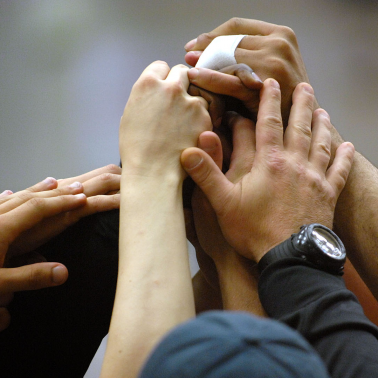 Teammates hands piled in group high five, various skin colors among them