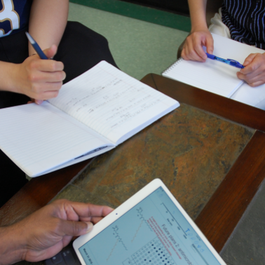 Closeup of hands, notebooks, pens while students and teacher gather around table