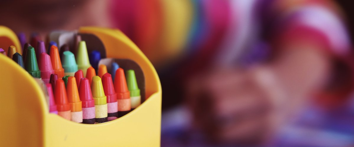 A box of colorful crayons with child in the background