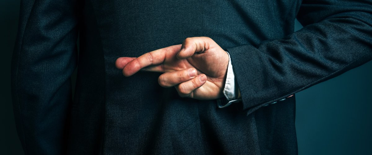 A person in a business blazer holds their fingers crossed behind their back