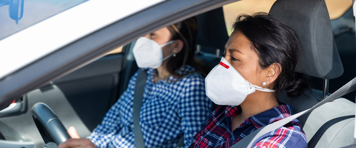 Two people in a car with face masks on