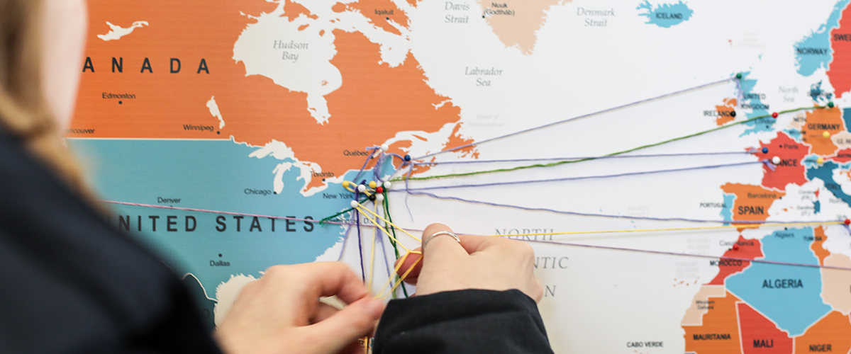 Closeup of pins on world map with threads strung between them