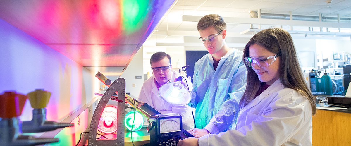 Three iCons students work with colored lights in a lab setting