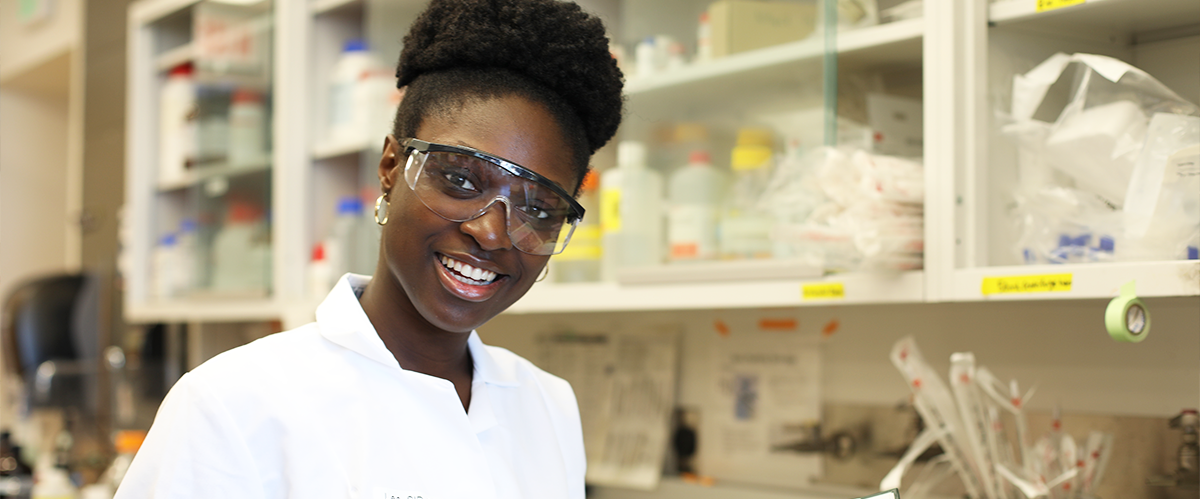 Student Kethney Massenat, in lab coat and safety goggles, consults her lab notebook in Peter Chien's lab