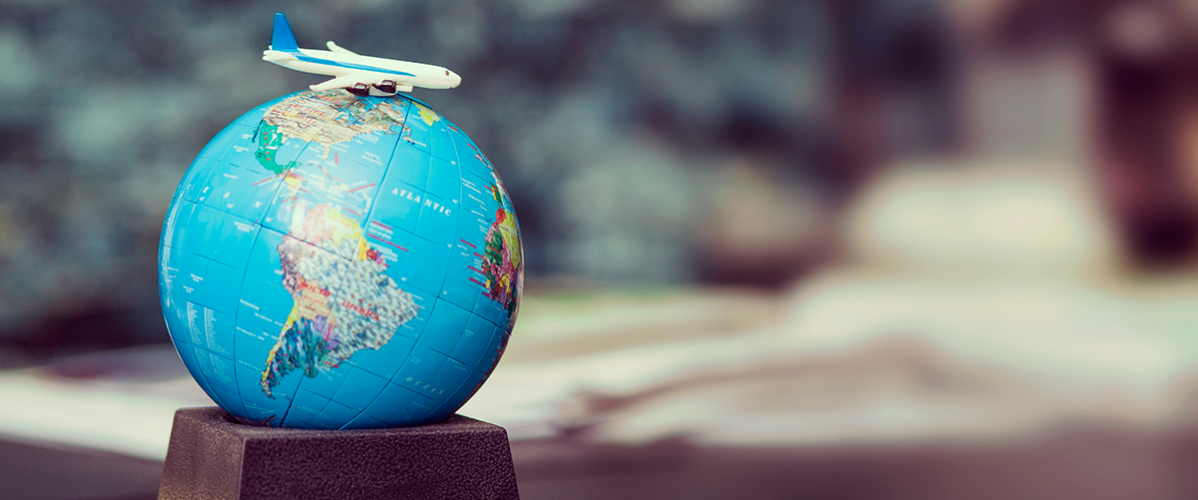 A small globe with a plane figurine sitting on top of it