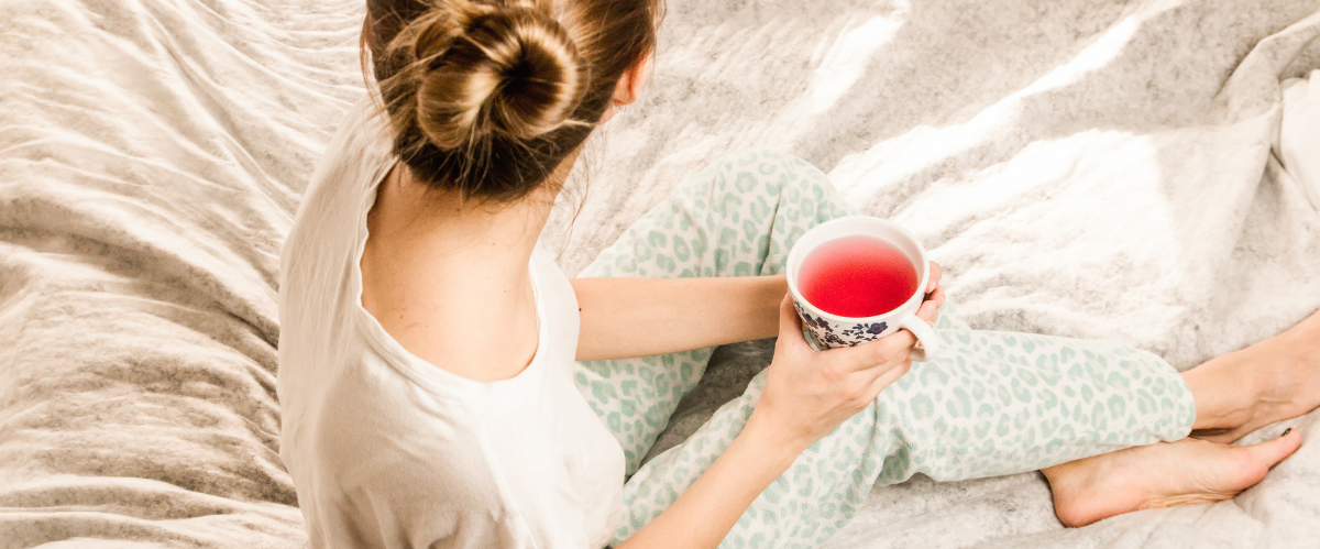 Woman wearing pajamas sits on bed holding a cup of tea
