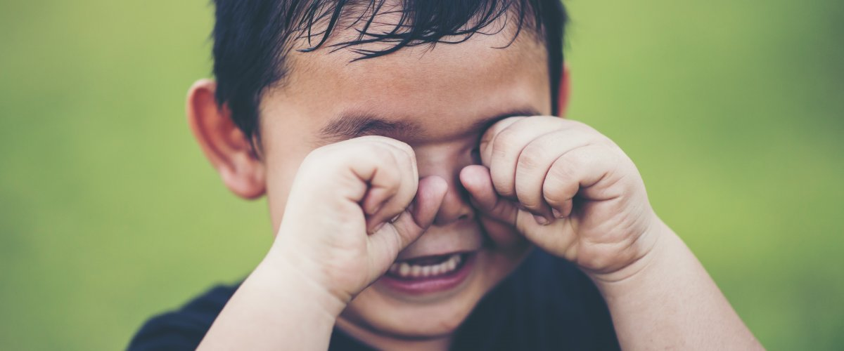 Tracking toddler tantrums - upset toddler boy rubs eyes
