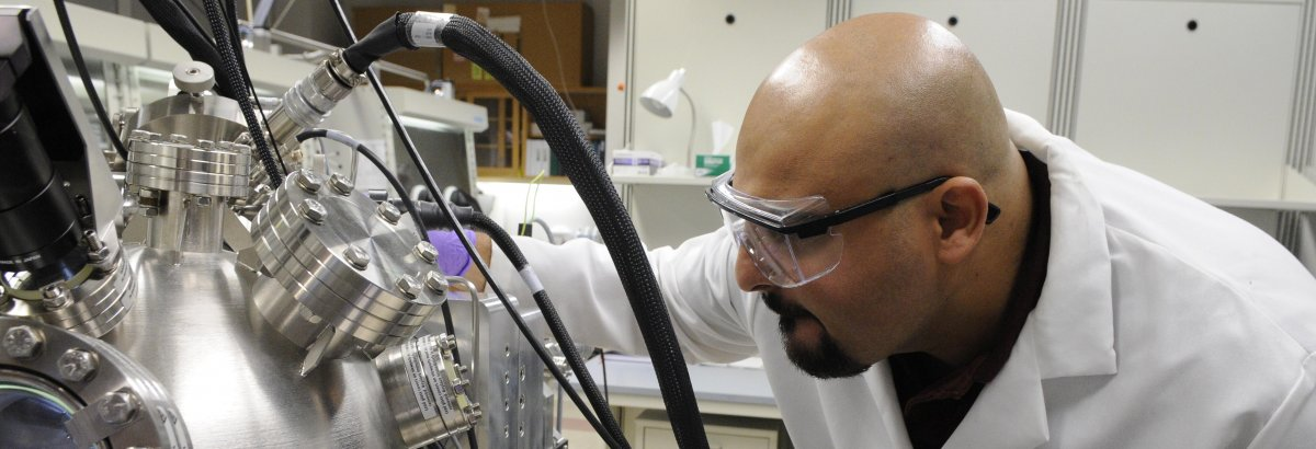 A faculty member works with lab equipment