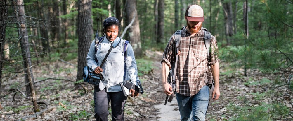 Two researchers, one black, one white, walk a forest trail