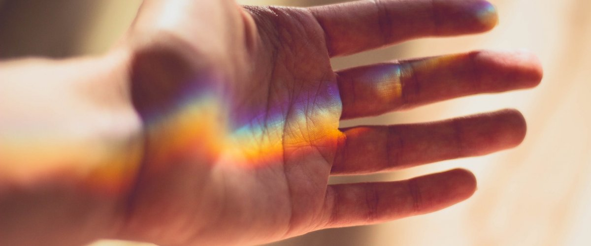 A hand with a rainbow in front of it