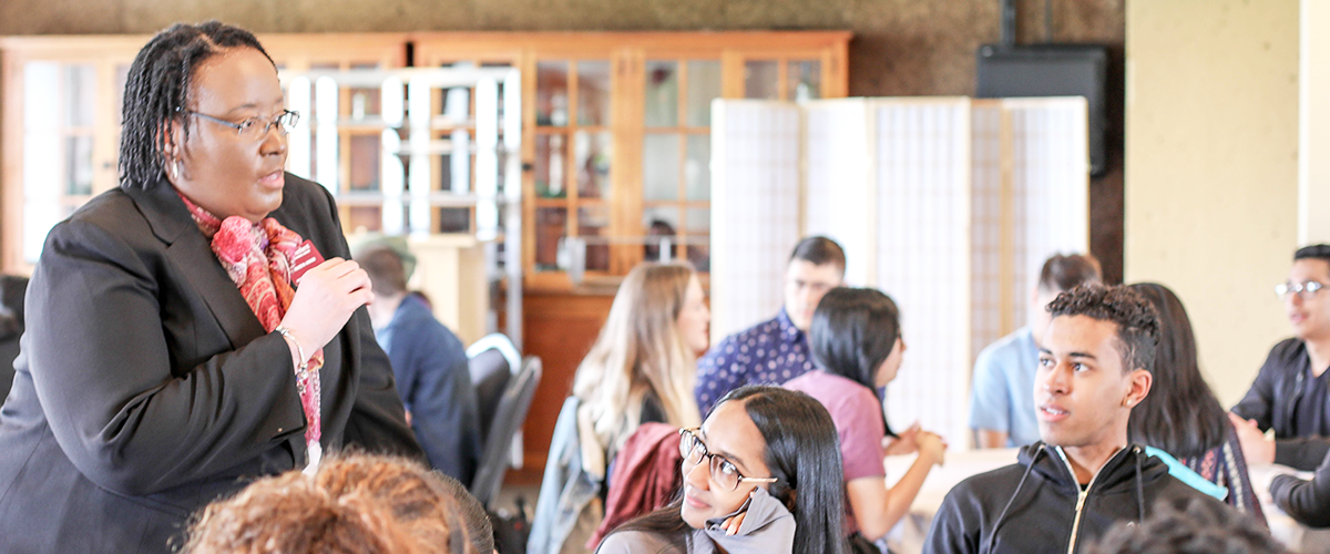 Tracie Gibson speaks to a table of students at summer undergraduate research kickoff luncheon, May 2019