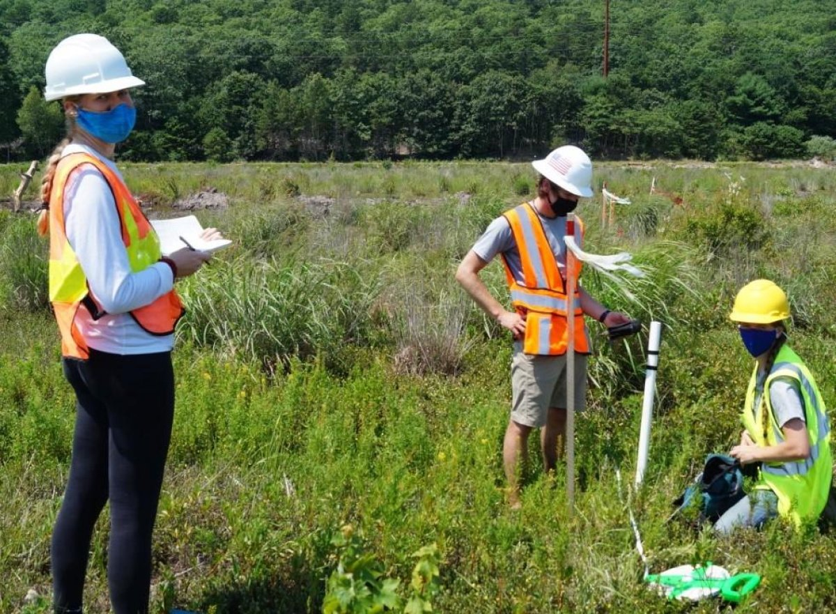 Students Alyssa Chase, Jeron LeBlanc and Lyn Watts measure soil moisture along a transect above fiber optic cables at Foothills